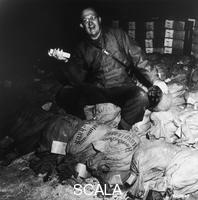 ********: The General Manton Eddy Sprague, commander of XII Corps U.S. Army, sitting on sacks of money with a gold bar in his hand. The Nazi army had hidden in salt mine Merkers, DM of the Reichsbank gold and works of art. Merkers to Kaiseroda / Rhoen. 15/04/1945. ********, *********** Permission for usage must be provided in writing from Scala.