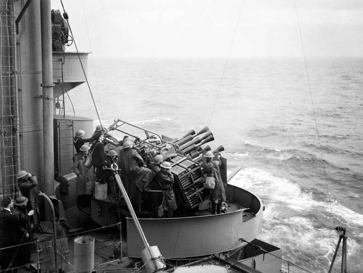 The port eight barrelled Vickers two pounder Mark VIII 'pom-pom' gun in action during anti-aircraft practice on board HMS RODNEY whilst she is at sea.