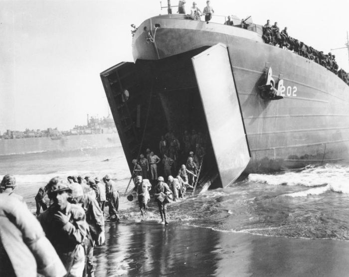 January 1944: U.S. Marines come ashore from the mouth of a Coast Guard manned LST, during the invasion of New Britain Island, at Cape Gloucester. (AP Photo)